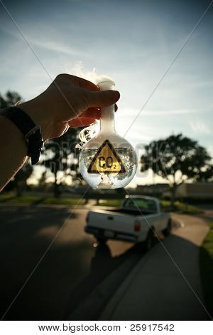 a Scientist holds a 500ml beaker filled with CO2 gainst the blue sky, with a truck in the background representing carbon emmissions from vechiles