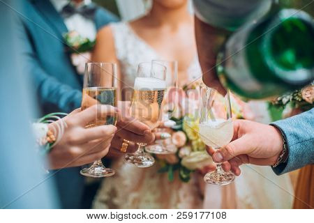 Groomsman Opens A Bottle Of Champagne Before Newlyweds Standing In The Park. Wedding Party In The Fo