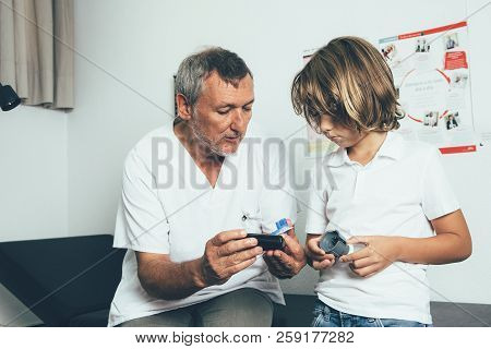 A Doctor Explains To A Young Diabetic Patient The Insulin Pump Functions In His Office. Child Diabet