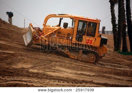 Seal Beach Califórnia, 20 de janeiro de 2010: bombeiros Bull tratores construir um burm areia na praia do selo
