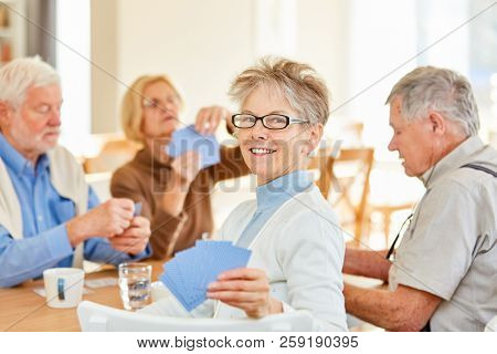 Senior woman and friends play cards together in retirement home and have fun