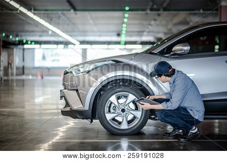 Young Asian Auto Mechanic Holding Digital Tablet Checking Car Wheel In Auto Service Garage. Mechanic