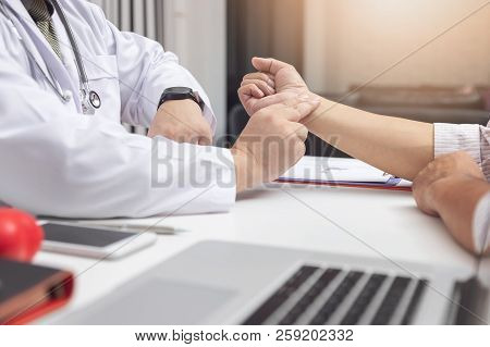Doctor Check Patient Blood Pressure In Office.