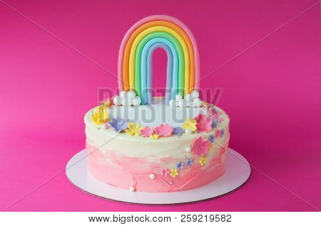 Birthday pink cake for girl, decorated with rainbow, clouds, flowers from mastic on a pink background. Cutout. Picture for a menu or a confectionery catalog. poster