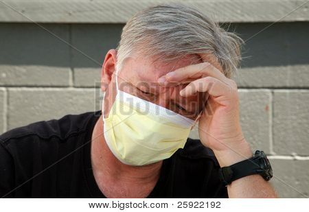 a man wears a yellow medical paper mask as he worries about how to stay safe from any air born illness