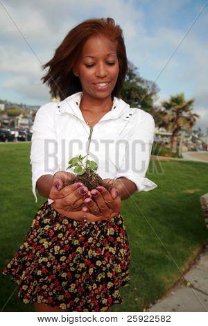 una hermosa mujer afroamericana tiene una planta verde en sus manos