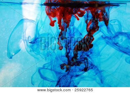 red and blue food coloring floats freely in a tank of clean clear water in a psychedelic pattern that is reminiscent of the early 1970's psychedelic period of history