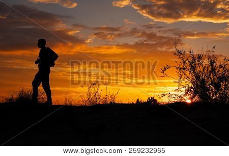 Silhouette Of Photographer With His Camera During Sunset