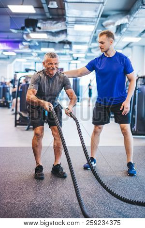 Senior man exercising at the gym with gym instructor. Personal training, healthy lifestyle.