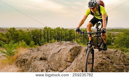 Cyclist Riding the Bike on the Autumn Rocky Trail at Sunset. Extreme Sport and Enduro Biking Concept.