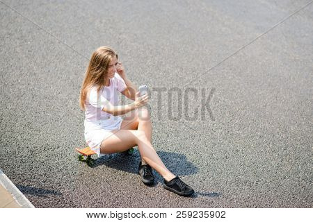 Young Beautiful Smiling Blonde Girl Making Selfie with Smartphone while Sitting on the Skateboard on the Road