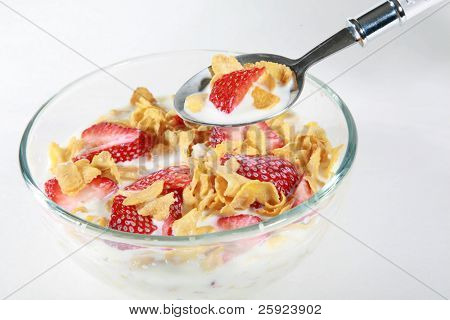 a clear glass bowl of corn flakes with strawberries and milk