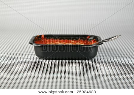 Hot fresh from the Microwave oven a Lasagna tv dinner sits on a black and white background waiting to be eaten by a hungry person about to watch their favorite tv program