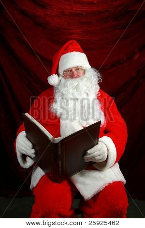 Santa Claus reads from his book his notes on all the