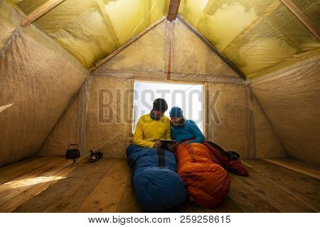 Two Happy Travelers Are Resting In The Old Mountain Hut, Sitting In A Sleeping Bags Next To A Window