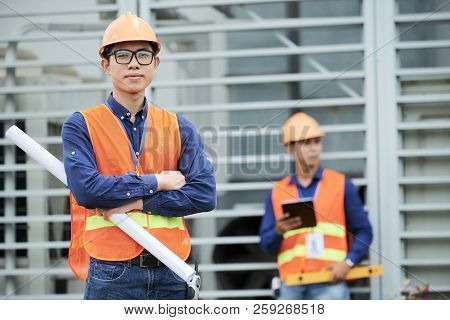 Attractive Asian Man In Helmet And Waistcoat Holding Draft And Looking At Camera While Standing On C