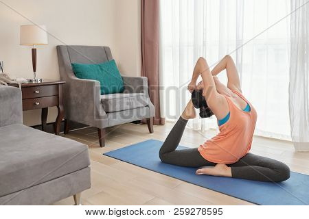 Side View Of Young Female Performing Difficult Yoga Pose While Sitting On Stretching Mat In Living R