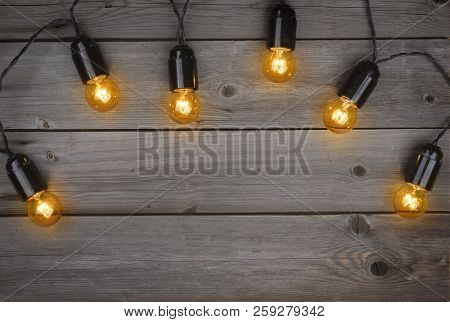 Christmas Glowing Electric Light Bulbs Garland On Dark Wooden Background