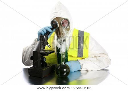 illegal drug mfg, chemical - a man in a hazmat suit, gas mask, and gloves and vest examines a dangerous chemical or drug he has manufactured in his laboratory. isolated on white room for your text