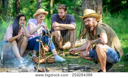 Friends Group Tourist Relaxing Near Bonfire. Hipster Roasting Sausage While Friends Sit On Log Shari