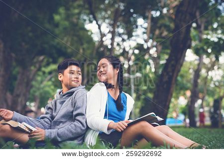 Happy Asian School Boy And Girl Turning Heads To Each Other While Sitting On Green Grass In Schoolya