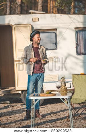 Happy Man Cutting Avocado Near Table With Wine And Pineapple, Vanlife In Nature