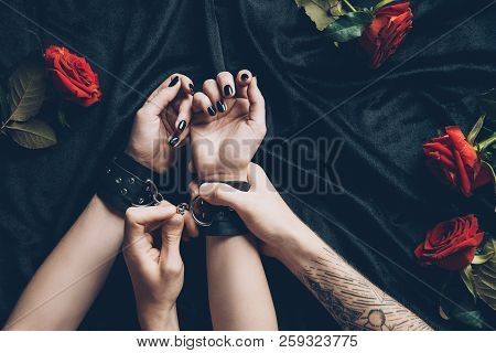 Cropped Shot Of Couple In Erotic Game With Black Leather Handcuffs