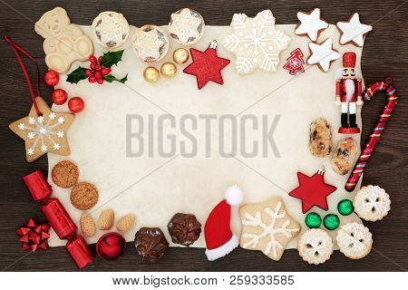 Christmas background border with festive symbols of tree decorations, biscuits, cakes, nuts, chocolates in foil and winter flora on parchment paper on rustic oak. Flat lay.