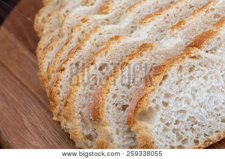 Close-up Of Sliced Bread. Rustic Looking On Wooden Board Background. Slices Of Village White Bread.