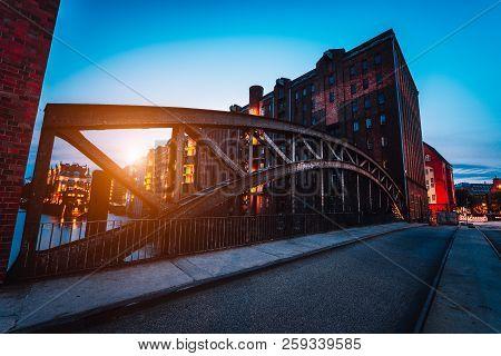 Poggenmuehlen Bridge At Dawn. Hamburg, Germany. Illuminated Buildings And Last Sunrays. Warehouse Di