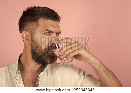 man with beard on face drink water from glass on pink background, healthcare and life source, hangover and thirst, refreshing, copy space poster