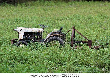 Forgotten Mower Rusting Away In An Overgrown Field.