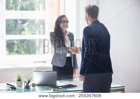 Smiling Young Businesswoman Shaking Hands With Her Partner In Office