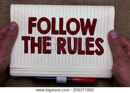 Handwriting text writing Follow The Rules. Concept meaning order someone stick to certain place country guides stricts Man hands holding notebook open page jute background Expressing ideas. poster