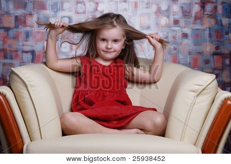 Little cute girl in red dress puling her hair.