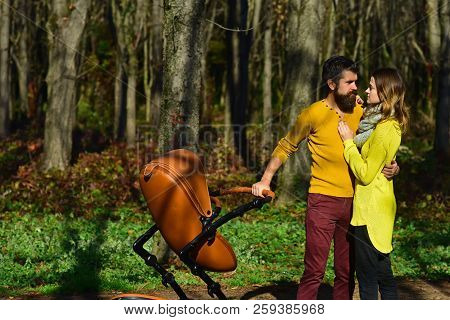 Family Values Concept. Loving Husband Kiss Wife With Baby Pram In Spring Park, Family Values. A Cele