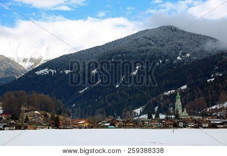 Panorama Of The Town Of Dobbiaco In Italy And In The Background The Snow-capped Mountains