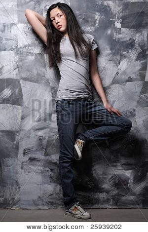 Young teenage girl posing in t-shirt and blue jeans on gray background.