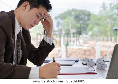 Depressed Business Man Looking Down When Inspection About Point Of Profit Loss On Business Report. N