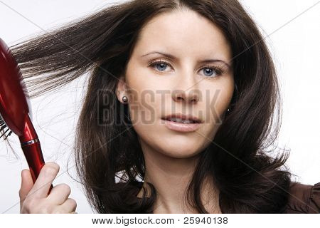Young attractive girl combing hair.