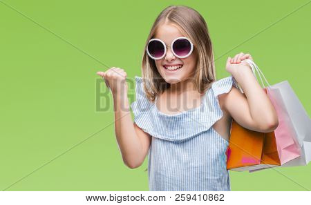 Young beautiful girl holding shopping bags on sales over isolated background screaming proud and celebrating victory and success very excited, cheering emotion