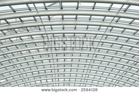 Curved reinforced steel roof joists in a conservatory with glass panes in between. poster