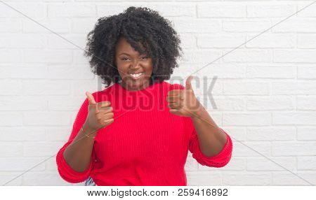 Young african american plus size woman over white brick wall success sign doing positive gesture with hand, thumbs up smiling and happy. Looking at the camera with cheerful expression, winner gesture.