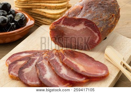 Piece of spanish Lomo Embuchado meat and slices
