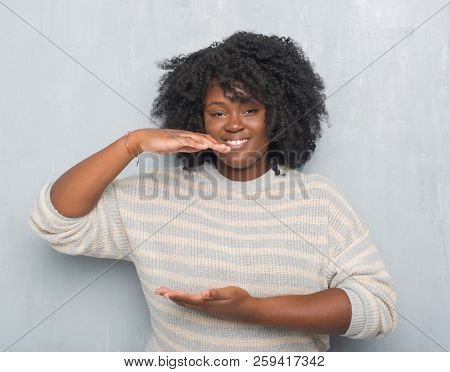 Young african american plus size woman over grey grunge wall wearing a sweater gesturing with hands showing big and large size sign, measure symbol. Smiling looking at the camera. Measuring concept.