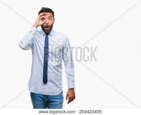 Adult hispanic business man over isolated background doing ok gesture shocked with surprised face, eye looking through fingers. Unbelieving expression.