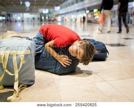 Kid sleeping on bags inside airport
