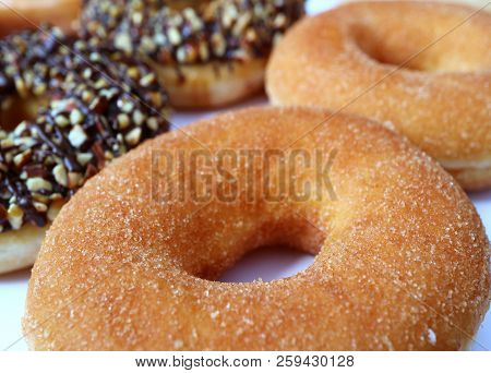 Closed Up Mouthwatering Cinnamon Doughnut With Blurred Almond Chocolate Doughnuts In Background