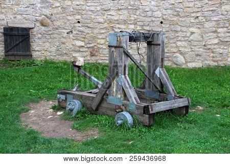 Ancient catapult on background of fortress wall