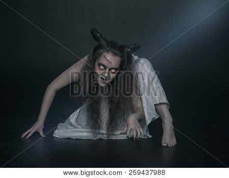 Terrible ghost with horns crawl on dark background poster